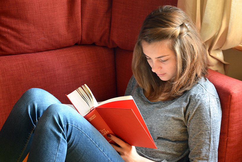Girl reading book on couch