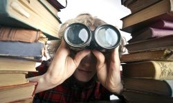 Boy with binoculars and books