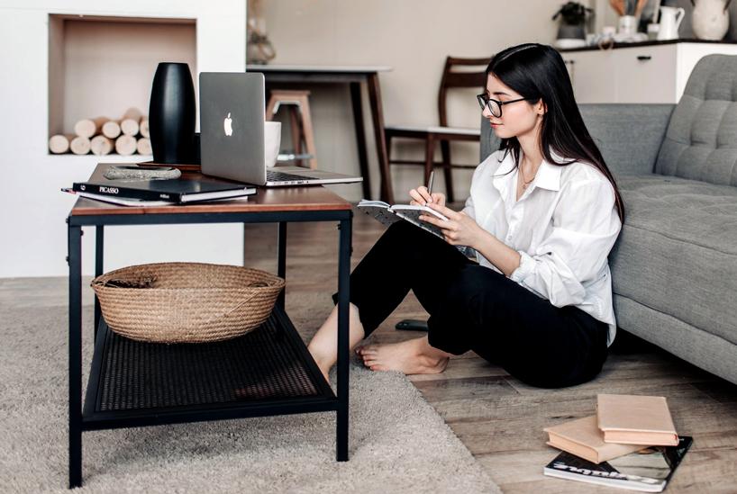 Woman taking notes at laptop